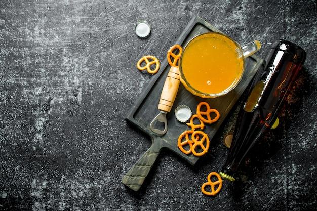 Cerveja em um copo em uma placa de corte com pretzels.