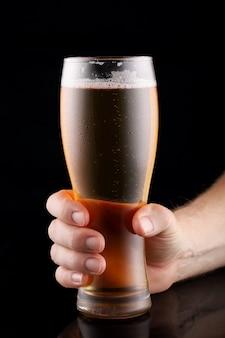 Cerveja em um copo na mão na superfície preta