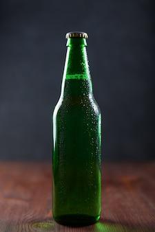 Cerveja em uma garrafa verde com água cai na mesa de madeira na parede escura