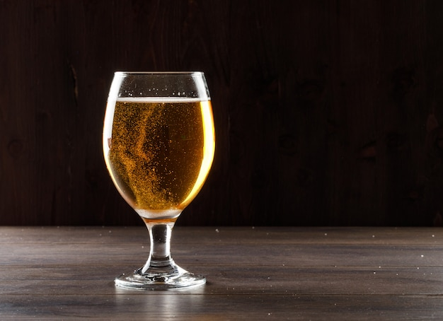 Cerveja em uma vista lateral de vidro de cálice em uma mesa de madeira