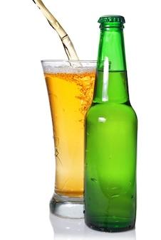 Cerveja escorrendo de um copo isolado com uma garrafa em branco