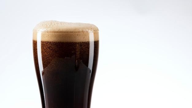 Cerveja escura com espuma close up