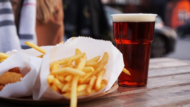 Cerveja escura e batata frita em mesa de madeira com comida para viagem na praça de alimentação