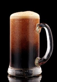 Cerveja escura em caneca de vidro com espuma