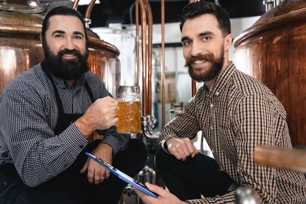 Cerveja feliz da bebida dos cervejeiros na fábrica da cerveja.