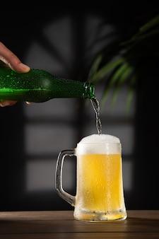 Cerveja fresca derramada em caneca de cerveja em base de madeira. formato vertical.