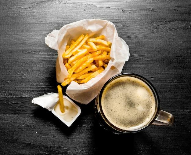 Cerveja fresca e batatas fritas com molho de mostarda no quadro-negro. vista do topo