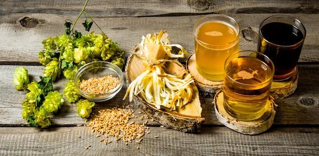 Cerveja fresca e o queijo salgado em uma mesa de madeira.