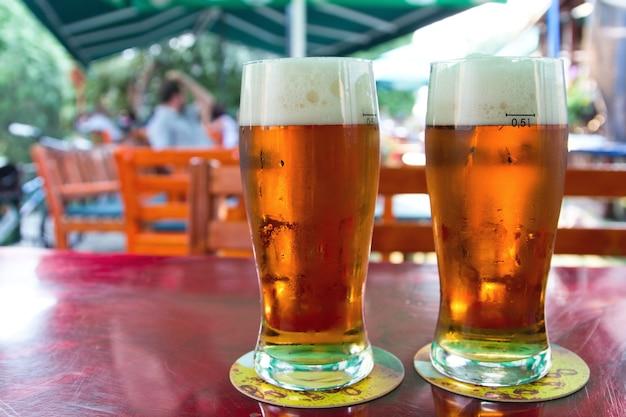 Cerveja fresca em copos orvalhados em pub local.