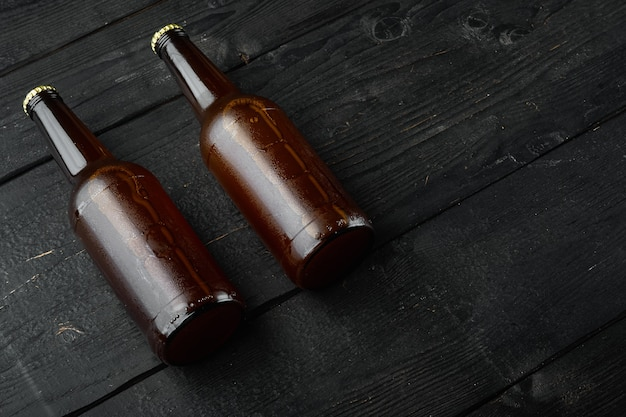 Cerveja fresca em garrafas de vidro em madeira preta