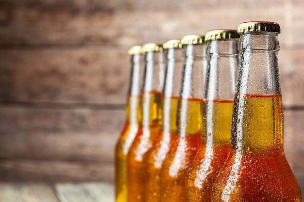 Cerveja fresca em garrafas de vidro em madeira