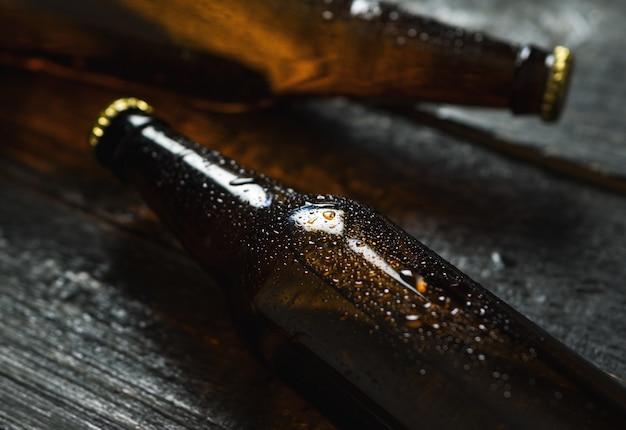 Cerveja gelada em garrafas de vidro na mesa de madeira