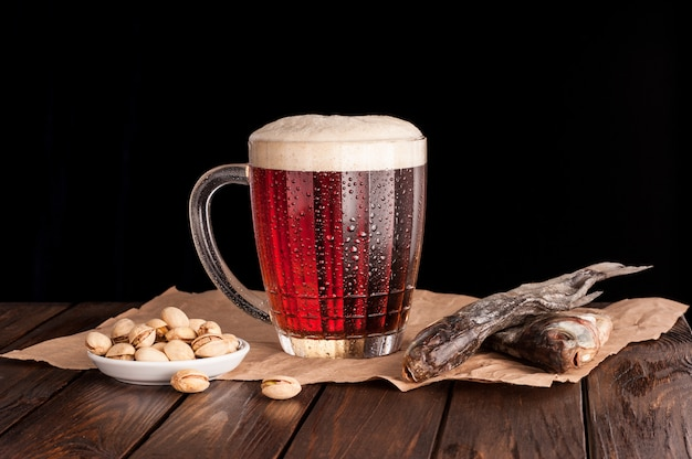 Cerveja gelada escura em uma caneca gelada na mesa de madeira escura