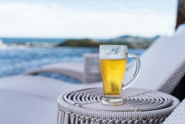 Cerveja gelada fresca em vidro na piscina com mar na cobertura. férias de férias em resort com consumo de álcool no verão.