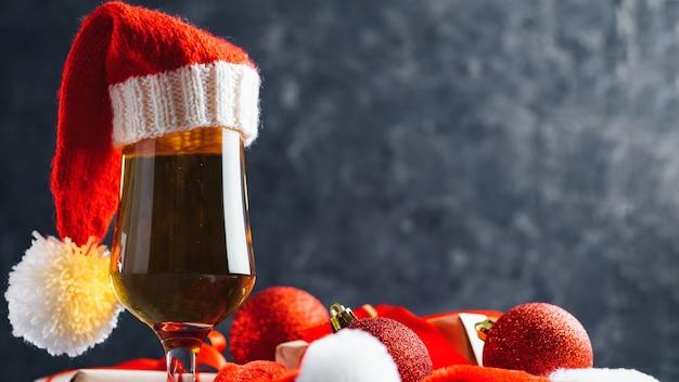 Cerveja lager com chapéu de papai noel em fundo escuro e presentes para o ano novo ou o natal