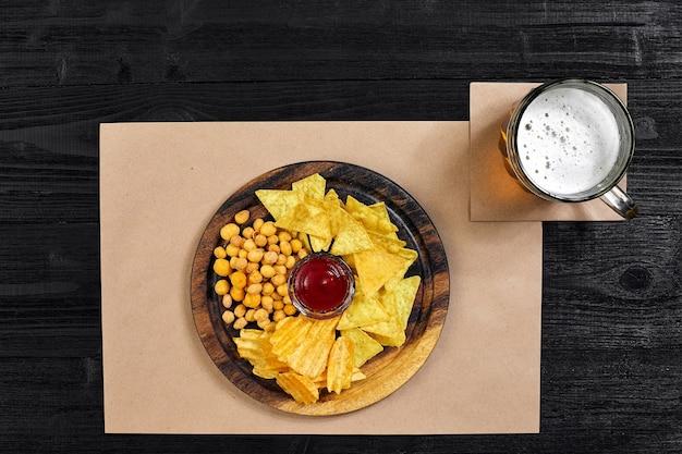 Cerveja lager e lanches na mesa de madeira preta, nozes, chips, vista superior com copyspace
