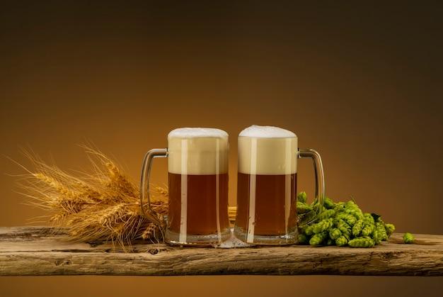 Cerveja light com espuma em canecas, lúpulo e trigo perto dos copos em cima da mesa
