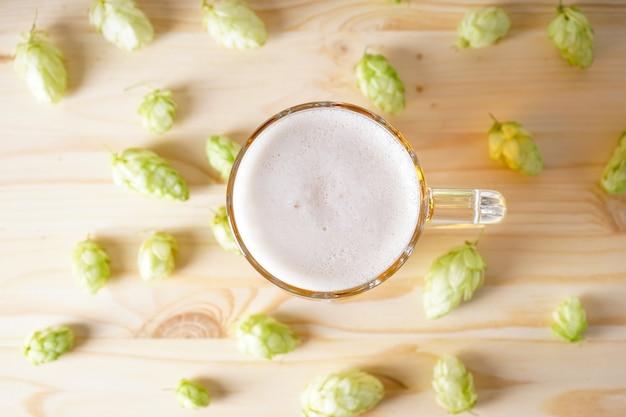 Cerveja light em um copo e cones de lúpulo em um espaço de madeira, vista de cima.