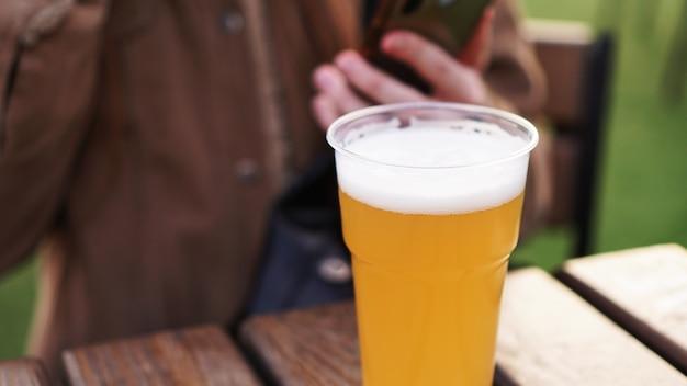 Cerveja light em uma garota de copo de plástico bebendo cerveja na praça de alimentação