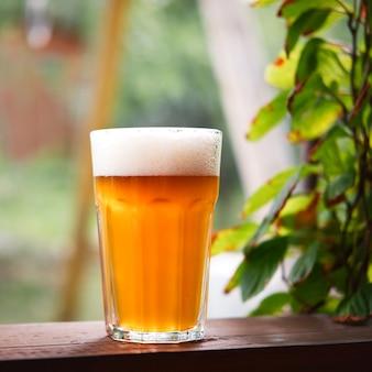 Cerveja light gelada com espuma branca em vidro na mesa de madeira com fundo borrado da natureza.