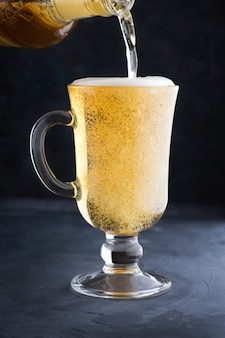 Cerveja light gelada com espuma em uma caneca de vidro derramando cerveja em um copo no balcão do bar ou pub