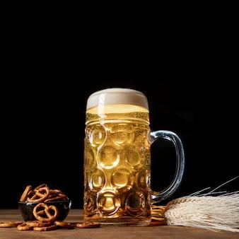 Cerveja loira close-up em uma mesa com pretzels