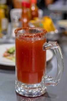 Cerveja michelada com clamato e tajin mexicano.