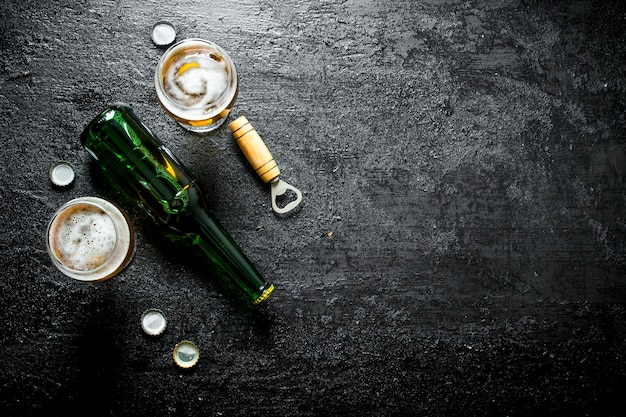 Cerveja na garrafa e dois copos de cerveja. sobre fundo preto rústico