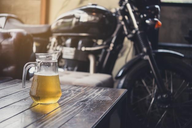 Cerveja na mesa de madeira com bigbike como pano de fundo.