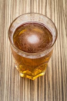 Cerveja no copo e tampas na mesa de madeira