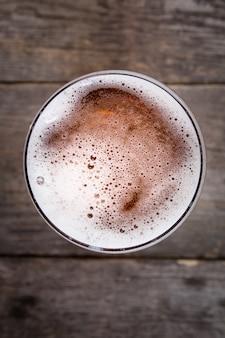Cerveja no copo. espuma de cerveja. vista de cima na mesa de madeira escura