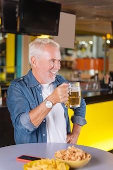 Cerveja saborosa. homem alegre e positivo segurando um copo de cerveja enquanto toma um gole