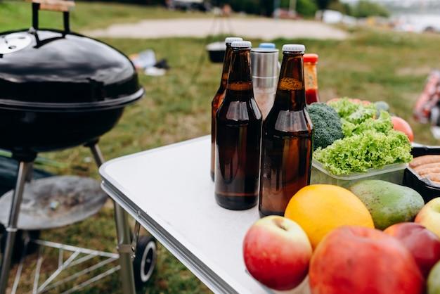 Cerveja, salsichas e legumes frescos na mesa ao ar livre ao lado do churrasco