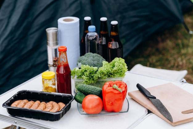 Cerveja, salsichas e legumes frescos na mesa ao ar livre