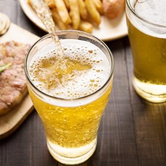 Cerveja sendo derramada em vidro com bife e batatas fritas no fundo de madeira