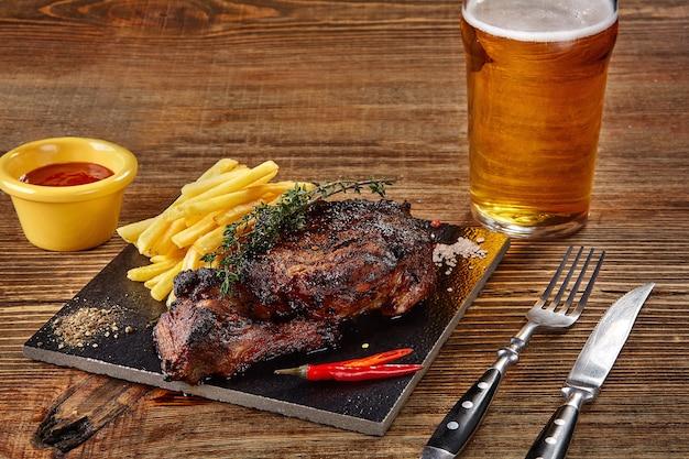 Cerveja sendo servida em um copo com bife gourmet e batatas fritas em fundo de madeira