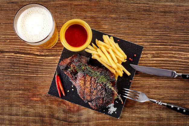 Cerveja sendo servida em um copo com bife gourmet e batatas fritas na vista superior do plano de fundo de madeira