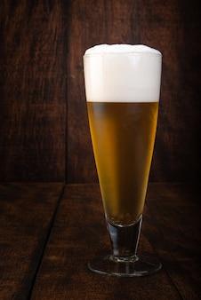 Cerveja servida em copo com fundo de madeira rústica.
