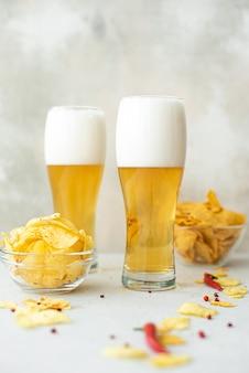 Cerveja tipo lager com batata frita picante em copos altos em uma mesa branca