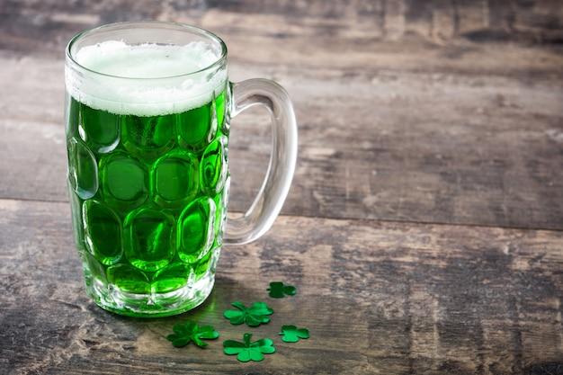 Cerveja tradicional do dia de são patrício verde no espaço da cópia de mesa de madeira