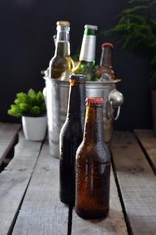 Cervejas diferentes sobre uma mesa de madeira. há garrafa e copo com gelo para mantê-los frios