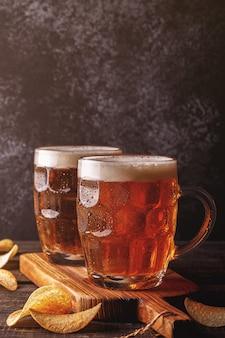 Cervejas geladas em vidro com chips em superfície escura