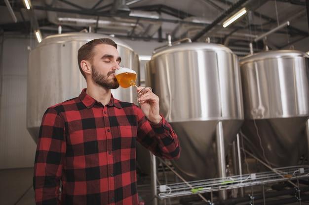 Cervejeiro degustando cerveja acabada de fazer em uma microcervejaria, tanques de metal no fundo
