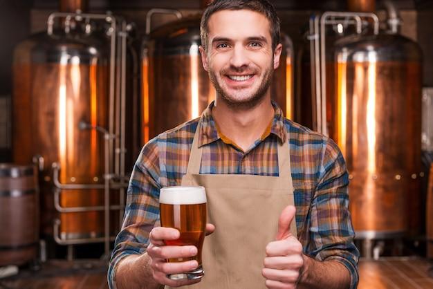 Cervejeiro feliz. feliz jovem cervejeiro de avental segurando um copo com cerveja e olhando para ele com um sorriso na frente de recipientes de metal