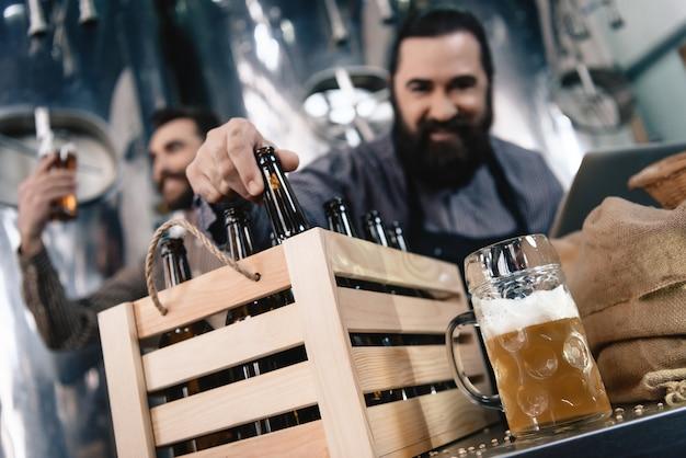 Cervejeiro feliz que inspeciona a cerveja na caixa de garrafas da caneca.