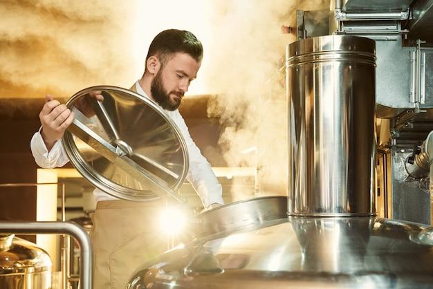 Cervejeiro, inspecionando o processo de fabricação de cerveja com vapor