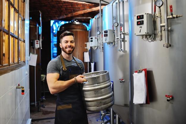 Cervejeiro masculino com um barril de cerveja de metal