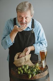 Cervejeiro sênior confiante com cerveja artesanal em vidro em um barril de madeira na parede cinza