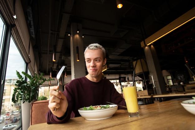 César calad muito saboroso! jovem alegre comendo alimentos saudáveis no restaurante e sorrindo.
