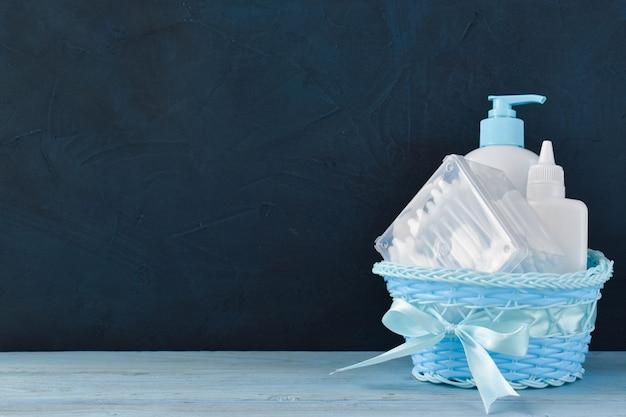 Cesta azul com produtos de higiene do bebê com espaço de cópia.